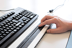 Foto: Detailed shot of a hand reading on a Braille display in front of a QERTY keyboard.